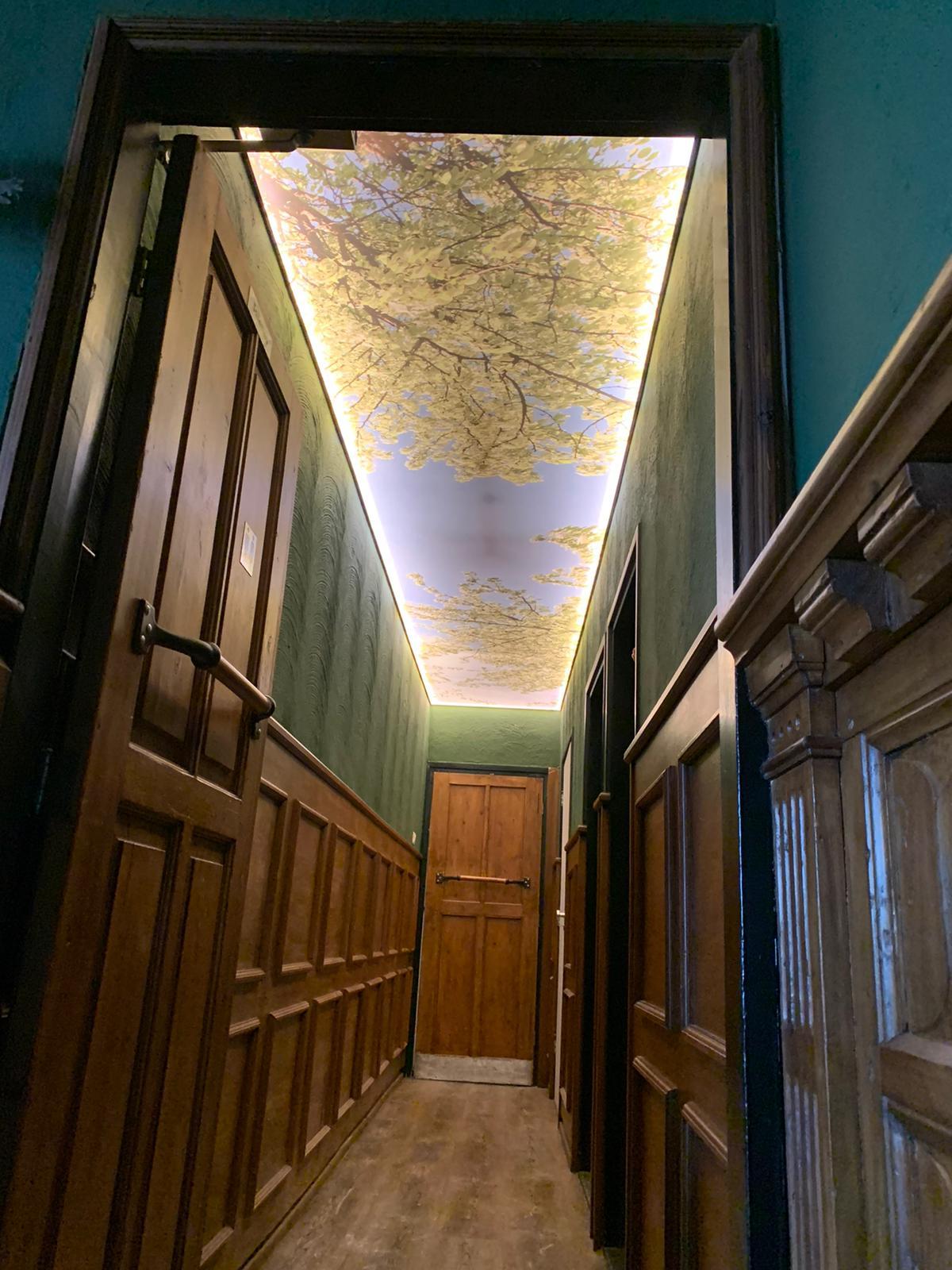 verlichte spanplafond in hal met print