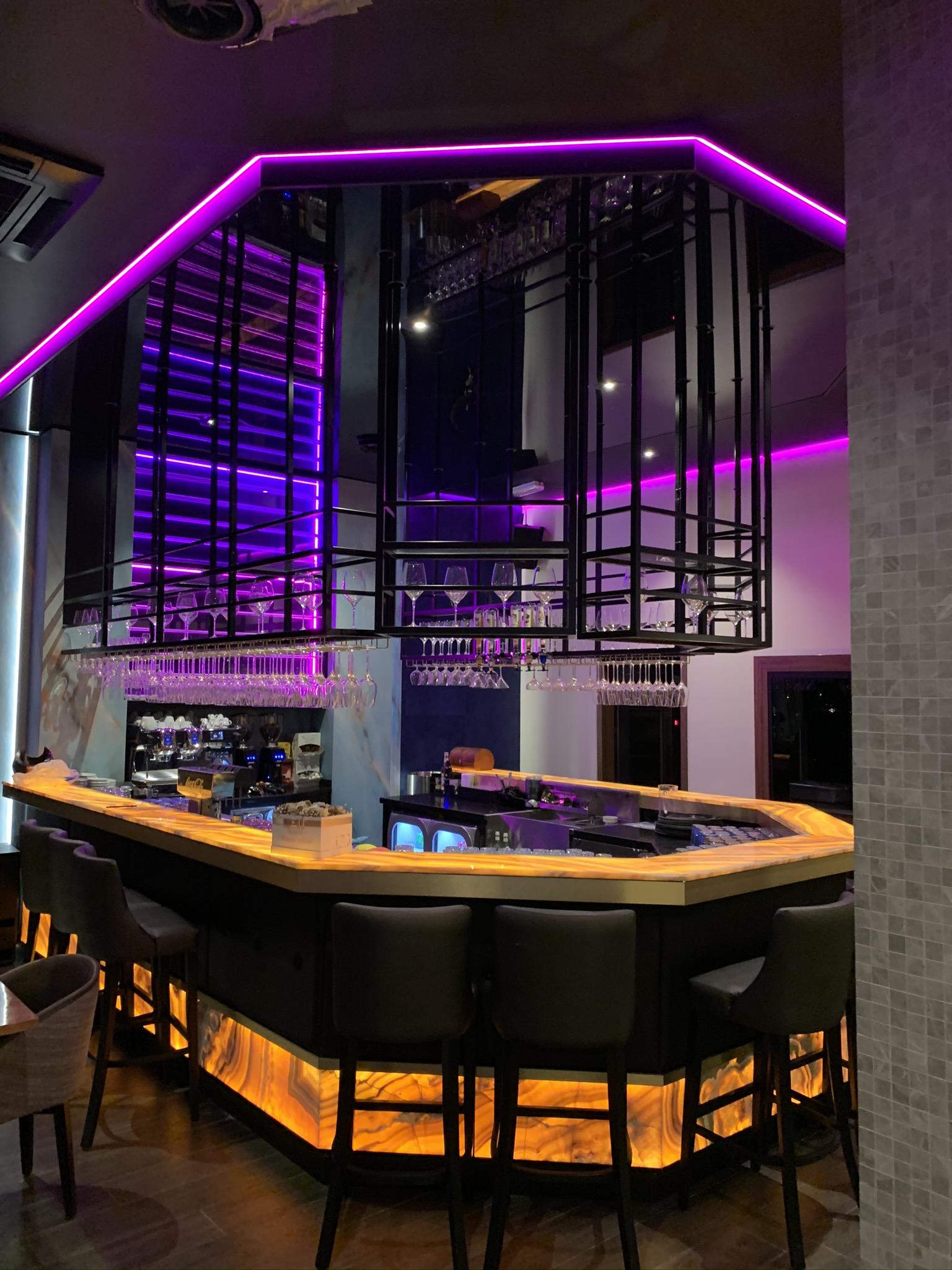 Gekleurde LED verlichting met een spanplafond in horeca